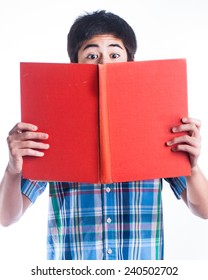 Young boy in blue plaid shirt reading a big book.