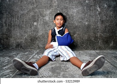 a young boy with blue sling on broken arm