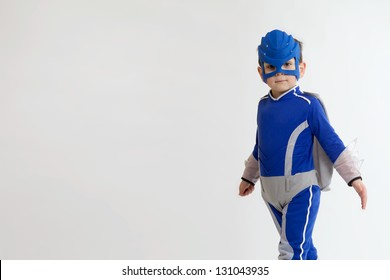 A Young Boy in a blue superhero suit with copy space