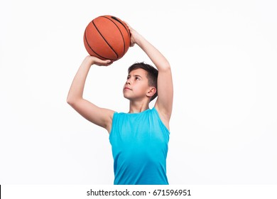 Young boy in blue t-shirt throwing up the ball with confidence isolated on white.