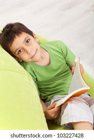 Young boy with a book - sitting on soft armchair