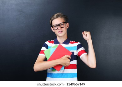 Young boy with books on blackboard background