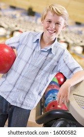 Young boy in bowling alley holding ball and smiling