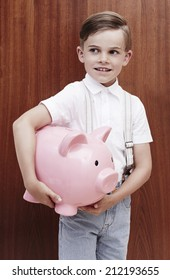 Young boy in braces holing large piggy bank