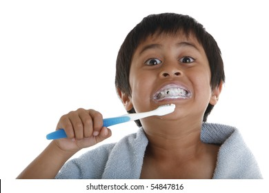 A young boy brushing his teeth. Studio shot  on white background.