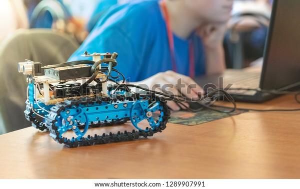 Joven construyendo un vehículo autónomo controlado por software