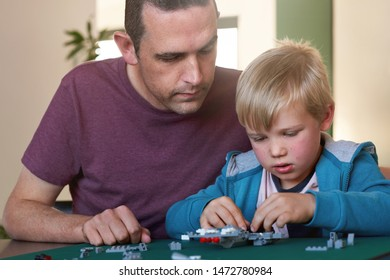 Young boy building model aeroplane from blocks, puzzle game mental stimulation father son activity