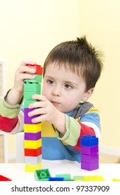 Young boy builds a tower with connecting blocks