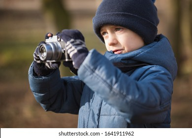 Young boy with camera taking pictures in the park