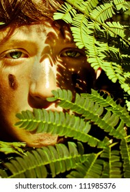 Young boy camouflaged behind tree leaves.
