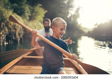 Young boy canoeing on the lake with his father