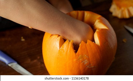 Young boy carving and painting a pumpkin for Halloween on a table