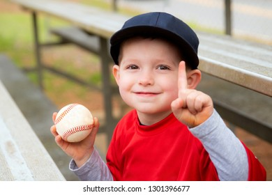 Young boy celebrating with game ball after baseball game