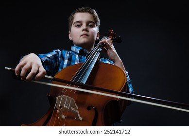 young boy Cellist playing classical music on cello