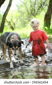 A young boy child and his German Shepherd mix dog are covered in mud and playing outside on the beach of a river in the woods.