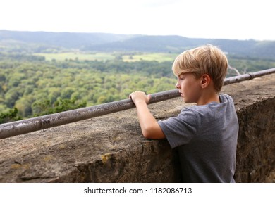 A young boy child is holding onto a railing as he looks over the edge of a cliff on a scenic tourist viewing deck at a State Park.