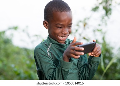 Young boy child with mobile phone outdoors. Child looking at the screen, playing, using apps.