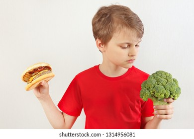 Young boy chooses between hamburger and broccoli on a white background