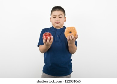 Young boy choosing between an apple and donut isolated over white background