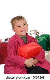 Young boy, with Christmas present on his lap, looking up with a happy, grateful expression, isolated on white