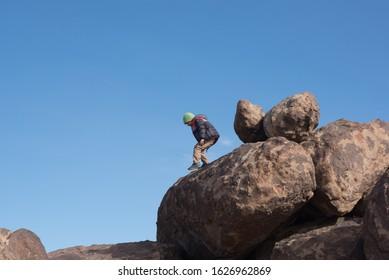 Young boy climbing rocks outdoors. Blue sky.