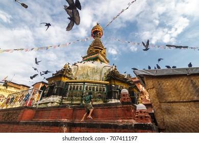 A young boy climbs up the Kathesimbhu Shree Gha Stupa in Kathmandu, Nepal.
