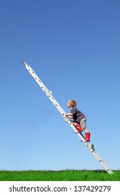 Young boy climbs a ladder on green meadow with blue sky