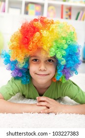 Young boy with clown wig laying on the floor smiling