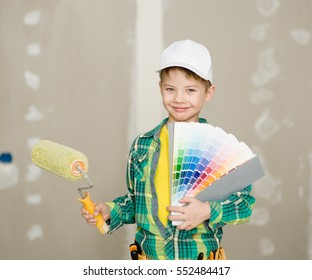 Young boy with color samples and paint roller