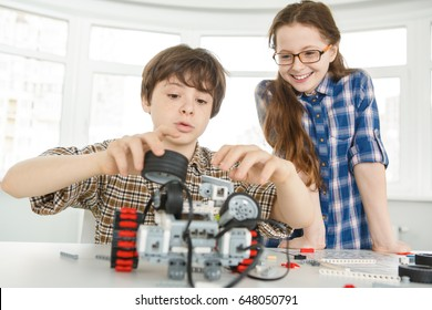 Young boy concentrating building a robot while his sister is smiling watching him standing near siblings kids children education learning lesson robotics school science hobby activity childhood family