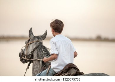 Young boy confident galloping horse on the field