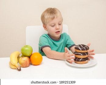 A young boy considers whether he will have a unhealthy donuts or some healthy fruit.  The child is photographed against a white background