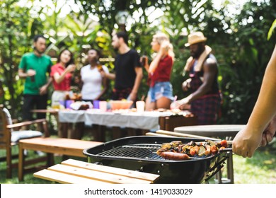 Young boy cooking meat on barbecue grill for Group of friends at summer outdoor party and holidays concept.