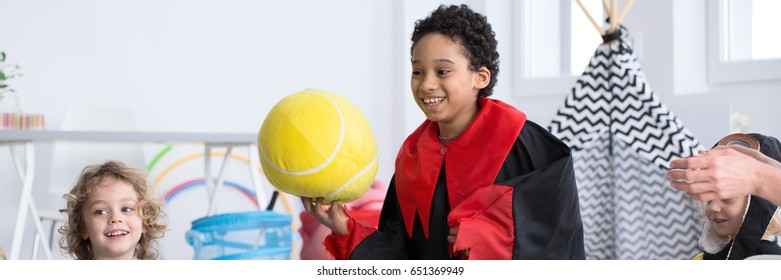 Young boy in costume holding a big yellow ball