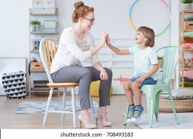 Young boy and counselor having fun during conversation in colorful room with toys