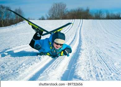 Young boy with cross-country skis lying on snow and smile