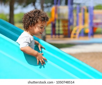 Young boy with curly hair has fun as he goes down a slide at a playground.