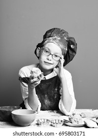 young boy cute cook chef in uniform and hat on stained face with glasses sitting on table with colorful bowls, tasty cookies, rolling pin and holding chocolate cake on red studio background