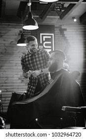 A young boy cuts man in the Barber shop