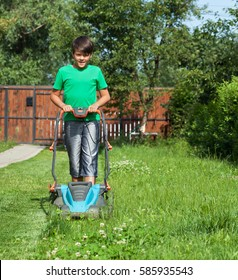 Young boy cutting the grass with a lawn mower in summer time