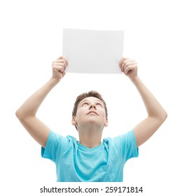 Young boy in a cyan t-shirt, holding an empty copyspace sheet of paper over his head, composition isolated over the white background