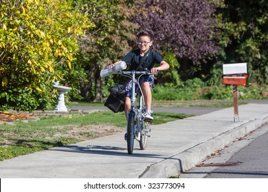 A young boy delivering newspapers on his bicycle