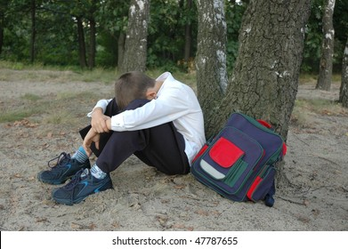 young boy depressed under the tree