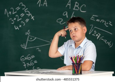 Young boy described at the green blackboard at school thinking about the task