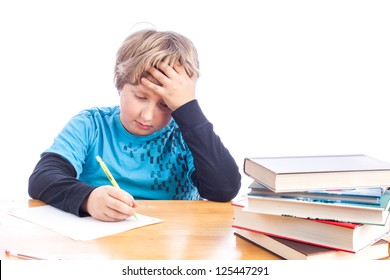 Young boy at a desk hand on his head frustrated doing homework. isolated on white with paper, books and desk. Space for your text.