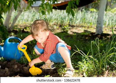 Young boy digging in the garden crouched down in the shade of a tree with his yellow toy spade digging into the fresh earth