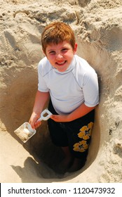 A young boy digs himself deeper into the sand on a summer's day