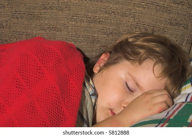 A young boy, with a dirty face, sleeping