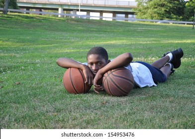 Young Boy Disgusted Looking at Camera Laying on Two Basketballs on grass in park