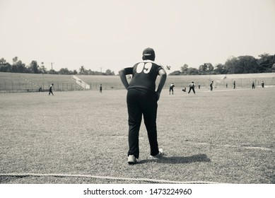 Young boy doing fielding practice around a sports ground